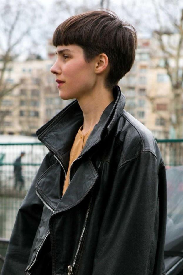 Femme aux cheveux coupés : plan de profil d'une femme de rue avec une coupe de bol brune, portant un manteau noir surdimensionné
