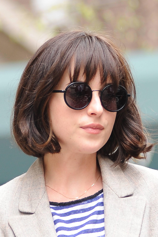 Gros plan de Dakota Johnson avec une coupe de cheveux de jeune fille française en désordre avec une frange floue, portant des lunettes de soleil rondes avec un trench-coat blanc