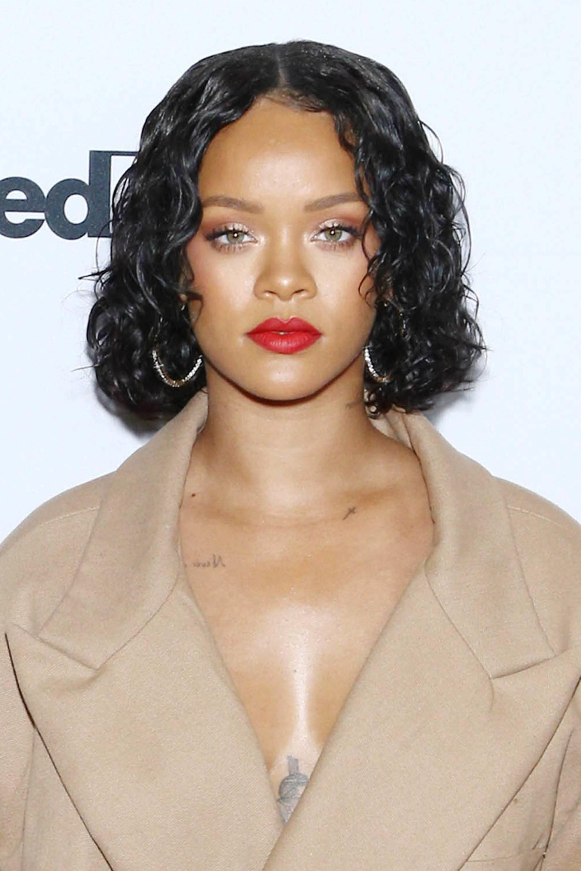 Rihanna sur le tapis rouge avec des cheveux noirs courts et bouclés, portant du rouge à lèvres rouge avec une veste de chameau et des boucles d'oreilles en forme de cerceau