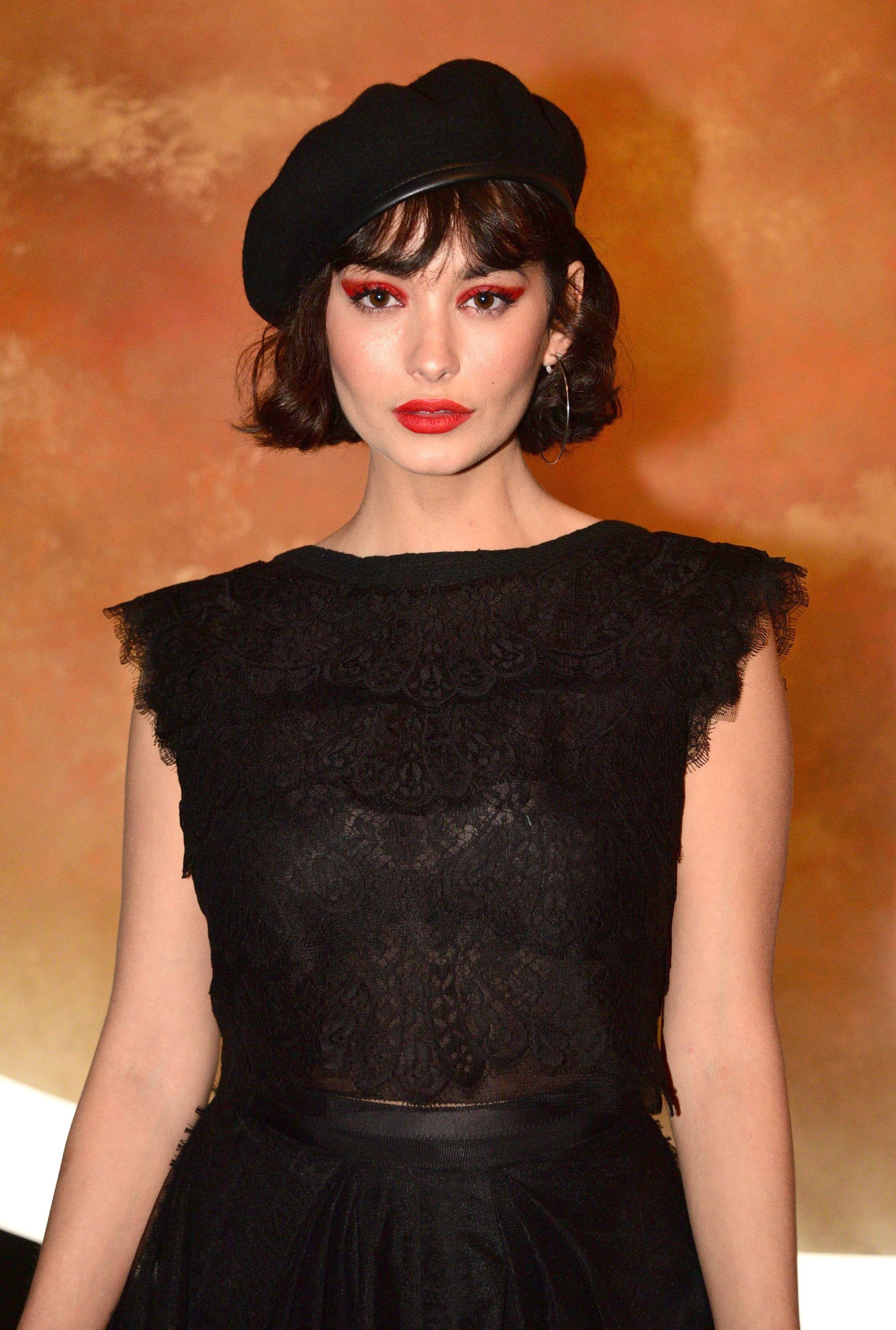 Coiffures de bob français : Taylor Lashae avec une coupe de bob courte avec une frange de soie, portant tout en noir avec un béret sur le tapis rouge