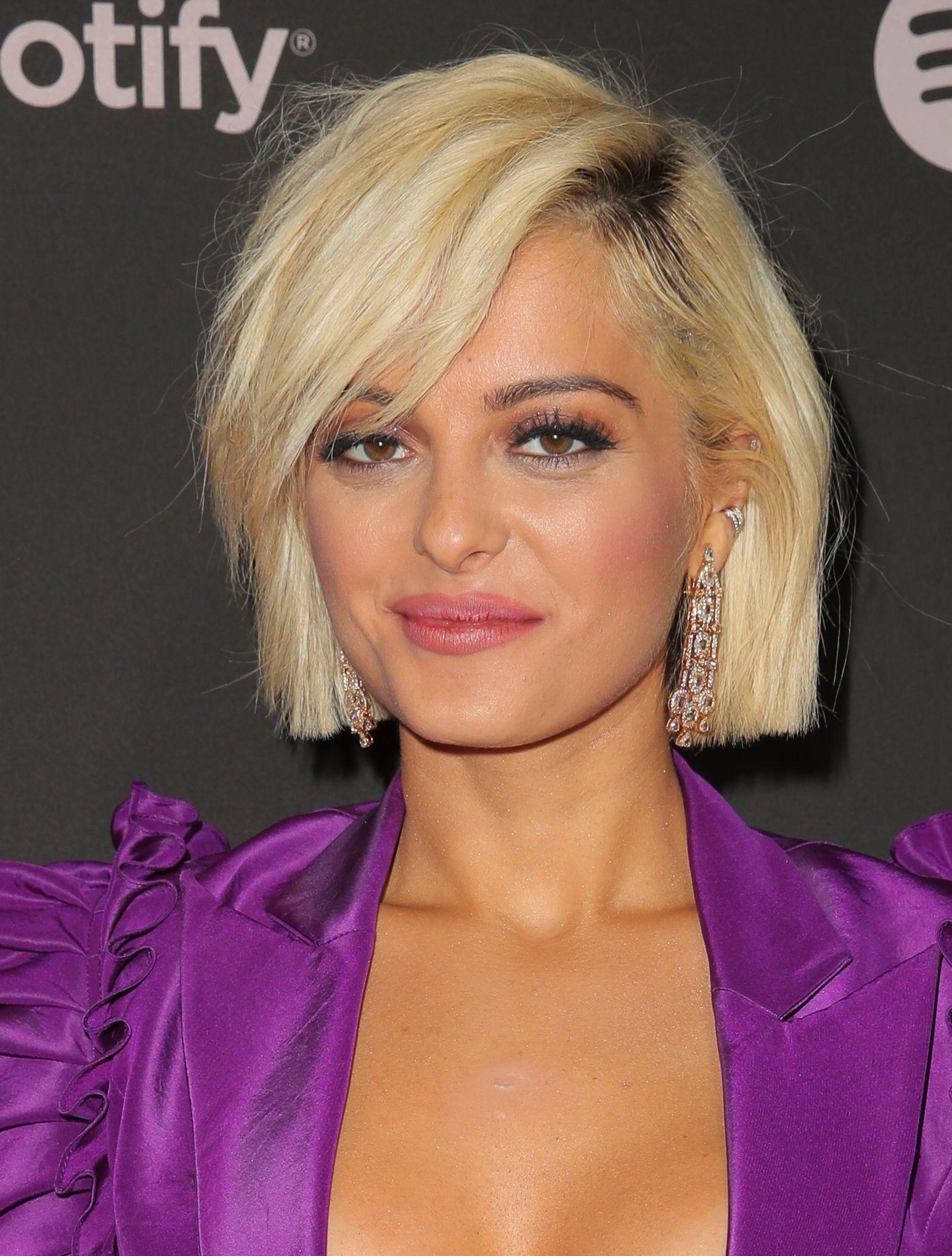 Bebe Rexha avec une courte coupe de bob blond doré avec une longue frange sur le côté