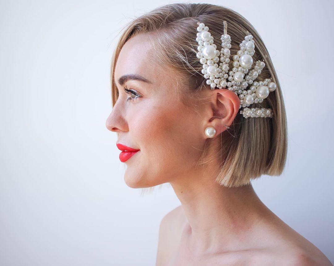 Femme au bob blond court avec des pinces à cheveux en perles
