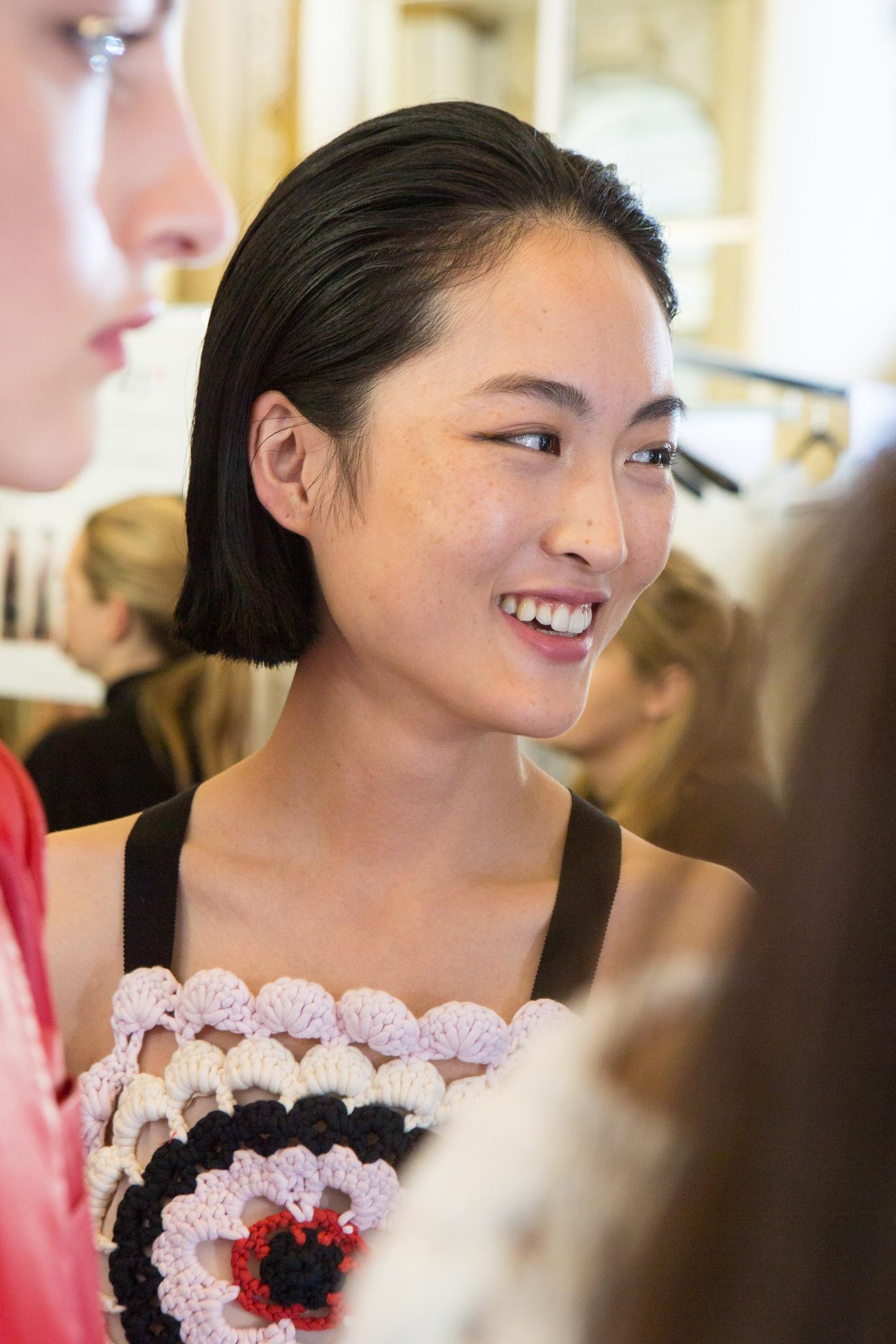 Une femme asiatique avec une coupe de cheveux au carré brun balayée vers l'arrière