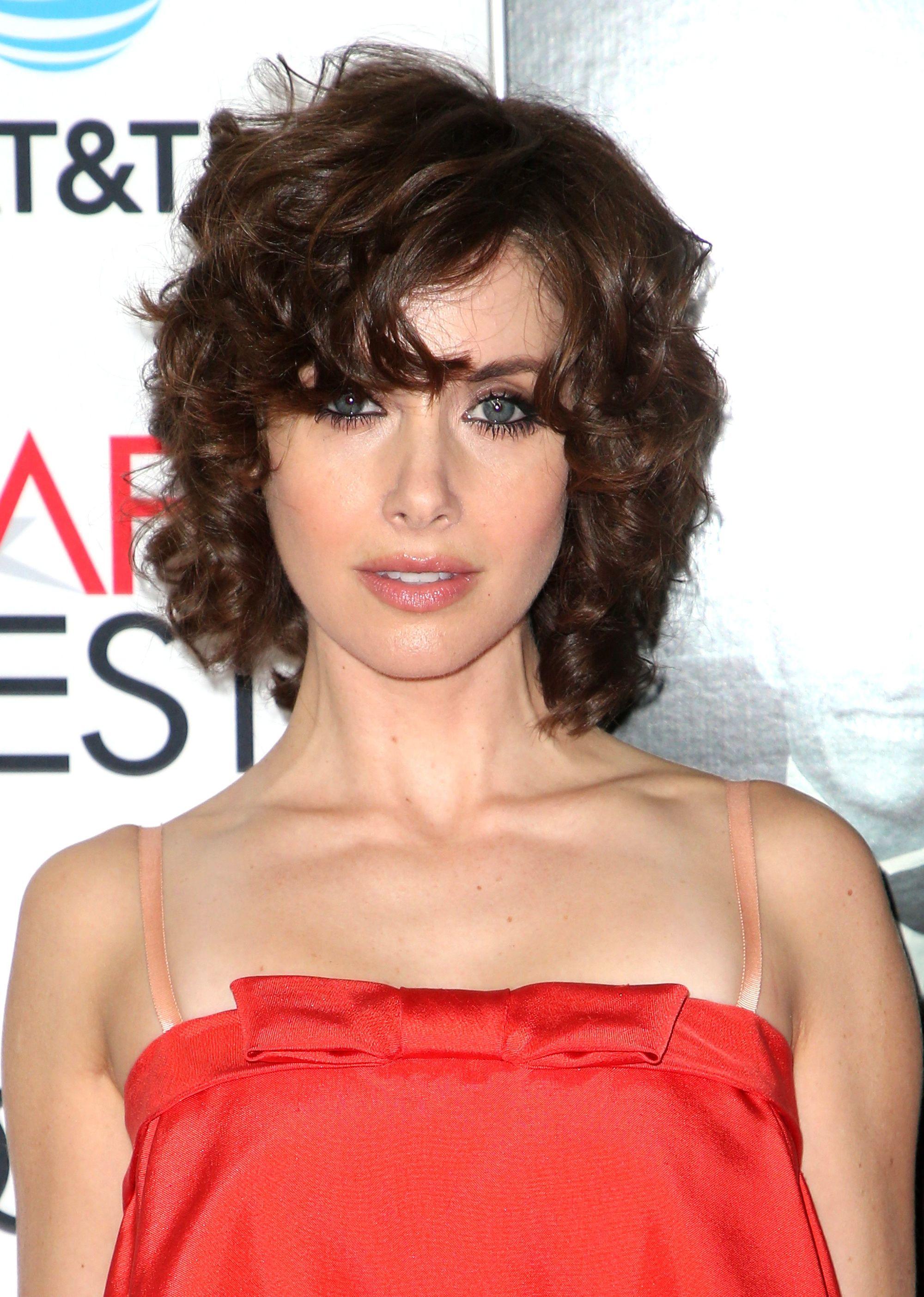 Les coiffures de Bob : Alison Brie avec des cheveux frisés et coupés au carré, portant une robe rouge sans bretelles sur le tapis rouge