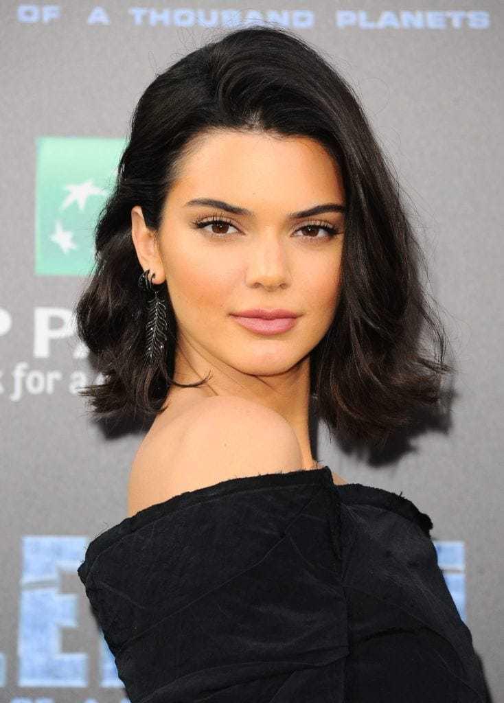 Les coiffures de Bob : Kendall Jenner avec une longue coupe de cheveux brun foncé en swoop bang, portant du noir sur le tapis rouge