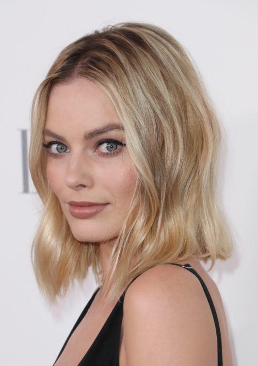 Margot Robbie avec de longs cheveux ondulés de bob de plage, portant un haut sombre à bretelles sur le tapis rouge