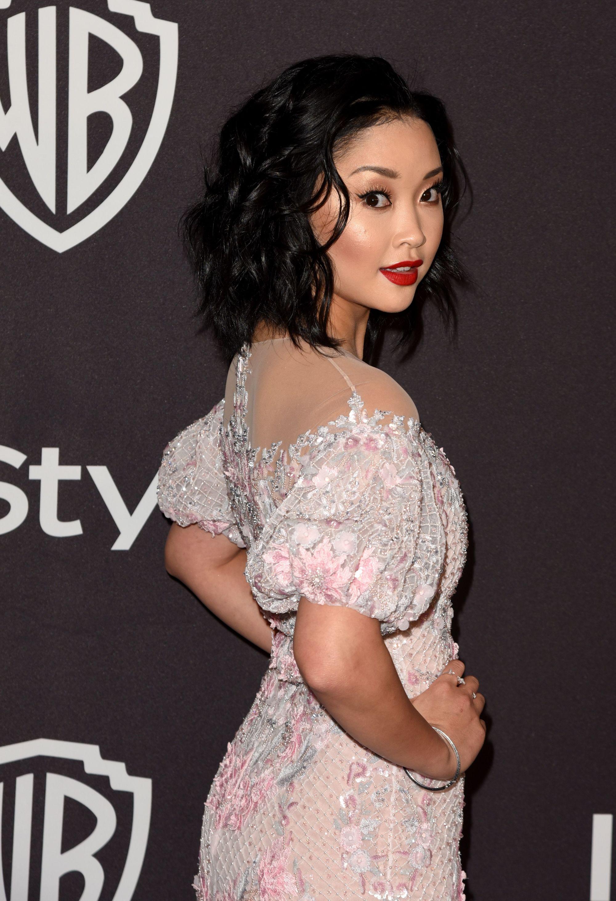 Lana Condor aux cheveux courts et ondulés brun foncé, portant une robe blanche et posant sur le tapis rouge