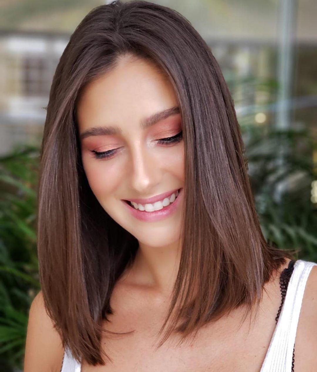 Femme avec une coupe de cheveux longs en chocolat