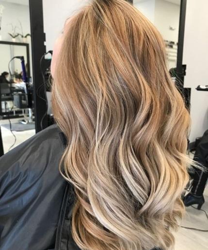 Vue de dos d'une femme dans le salon avec de longs cheveux bouclés blonds sableux à la fraise