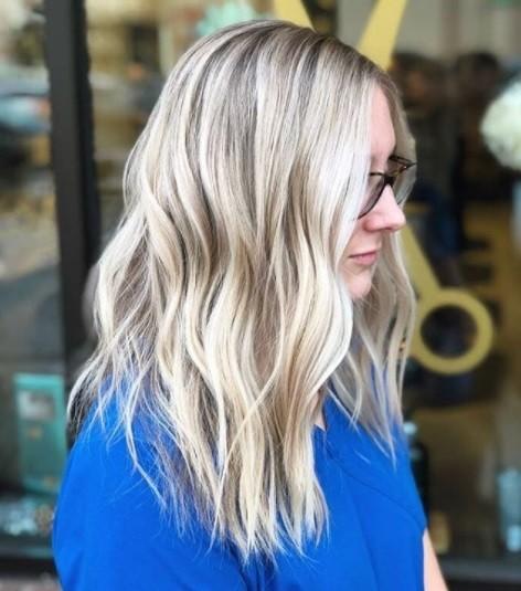 profil latéral d'une femme avec des cheveux ondulés blond cendré à la longueur de la poitrine