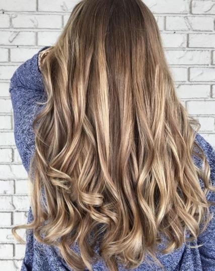vue de dos d'une femme aux cheveux blonds bruns bouclés avec des mèches et des lumières basses
