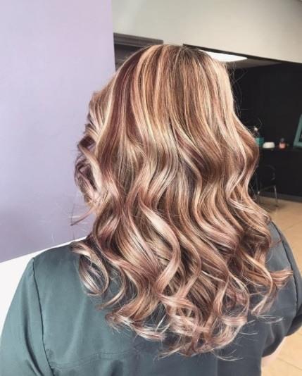 Vue de dos d'une femme dans le salon avec des cheveux bourgogne rouge et blond bouclé