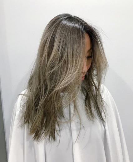 femme asiatique aux cheveux gris foncé argenté avec des décolletés brun foncé plus foncés
