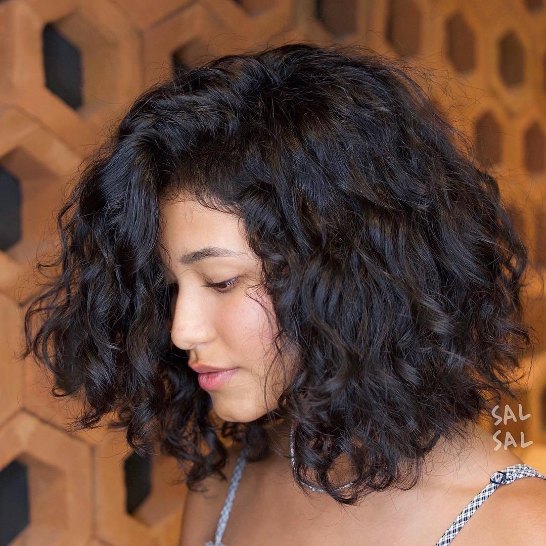 femme aux cheveux bruns bouclés naturels, coupés en lob asymétrique