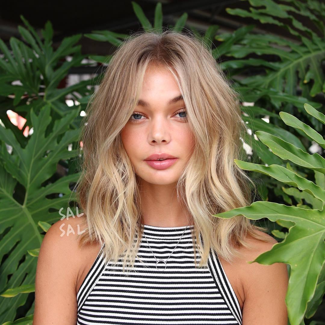 Femme aux cheveux blonds en plage, coiffée en lob ébouriffé