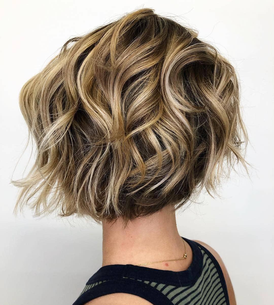 Bob diplômé : Femme avec une coiffure de bob diplômé courte et houleuse dans un studio