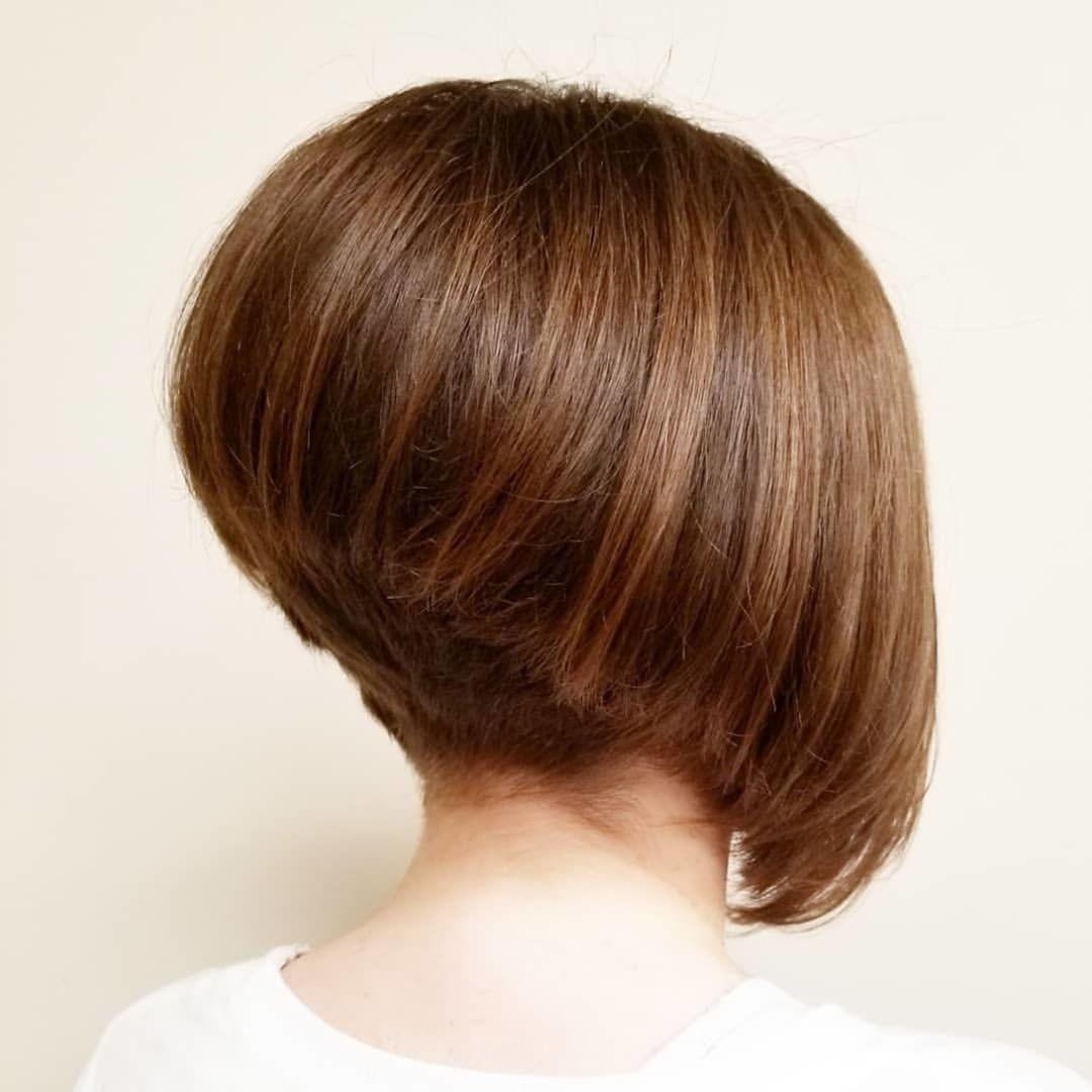 Coiffure au carré diplômée : Femme au bob gradué marron avec une coiffure en contre-dépouille dans un studio