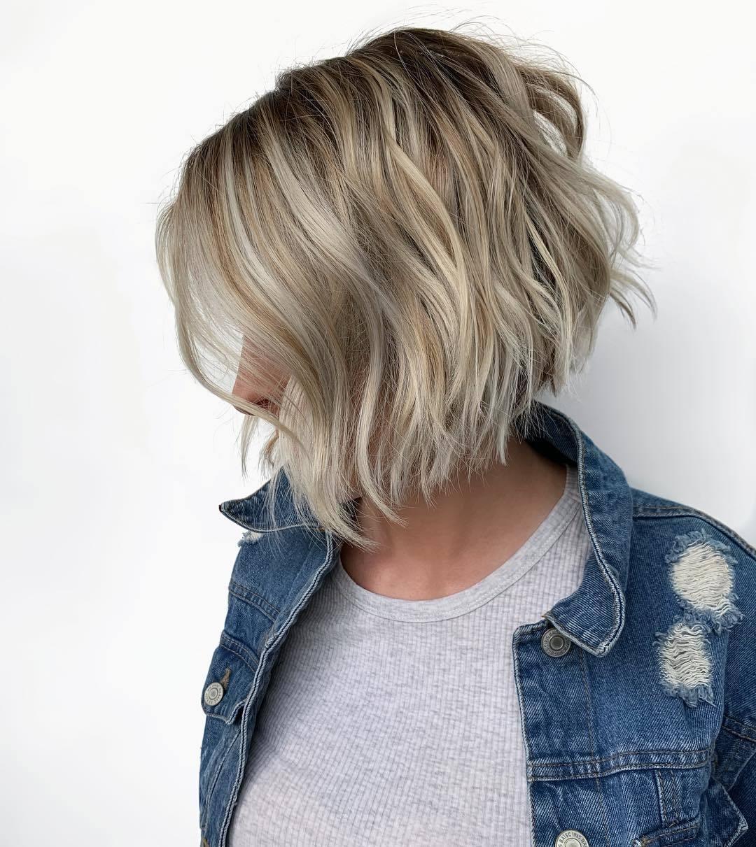 Femme au bob gradué ondulé d'un blond cendré, portant un top gris et un denim en studio
