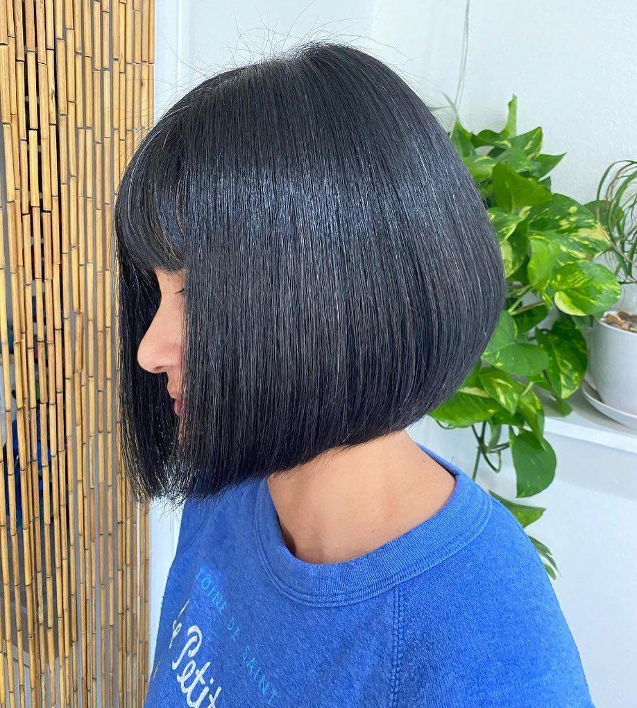 Femme avec une coupe de cheveux sombre et graduée avec une frange complète