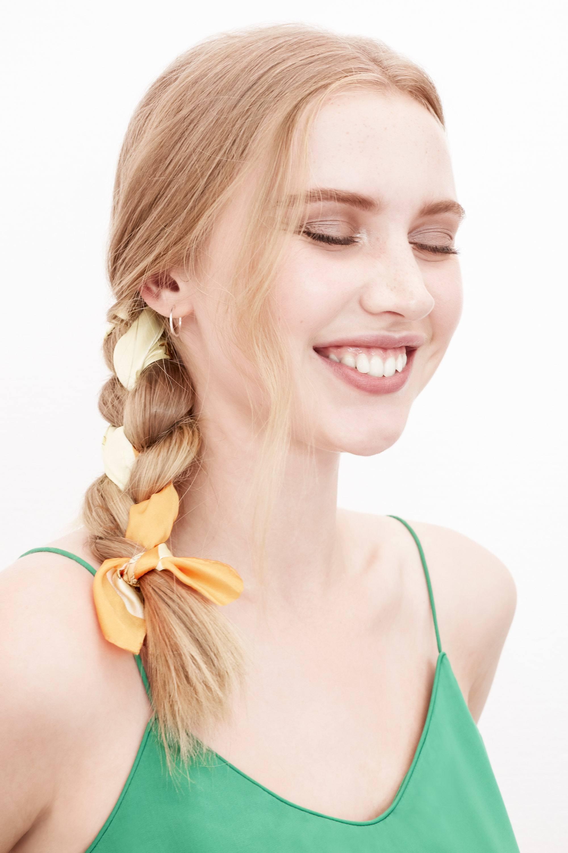 Des tresses faciles pour les cheveux longs : Photo d'une femme blonde avec une tresse de côté avec un ruban jaune, portant un cami top vert
