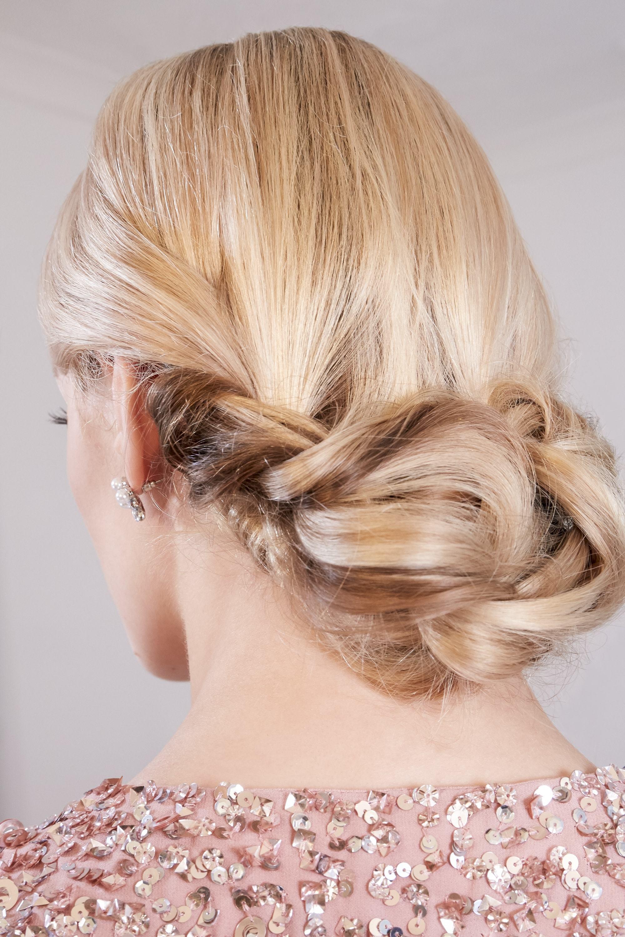 Des tresses faciles pour les cheveux longs : Vue de dos d'une femme blonde avec un chignon bas et tordu, portant une robe à paillettes roses