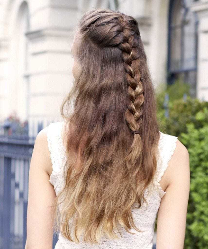 Des tresses faciles pour les cheveux longs : Vue de dos d'une femme aux cheveux longs ondulés de couleur brune ombre dans une coiffure tressée à mi-hauteur
