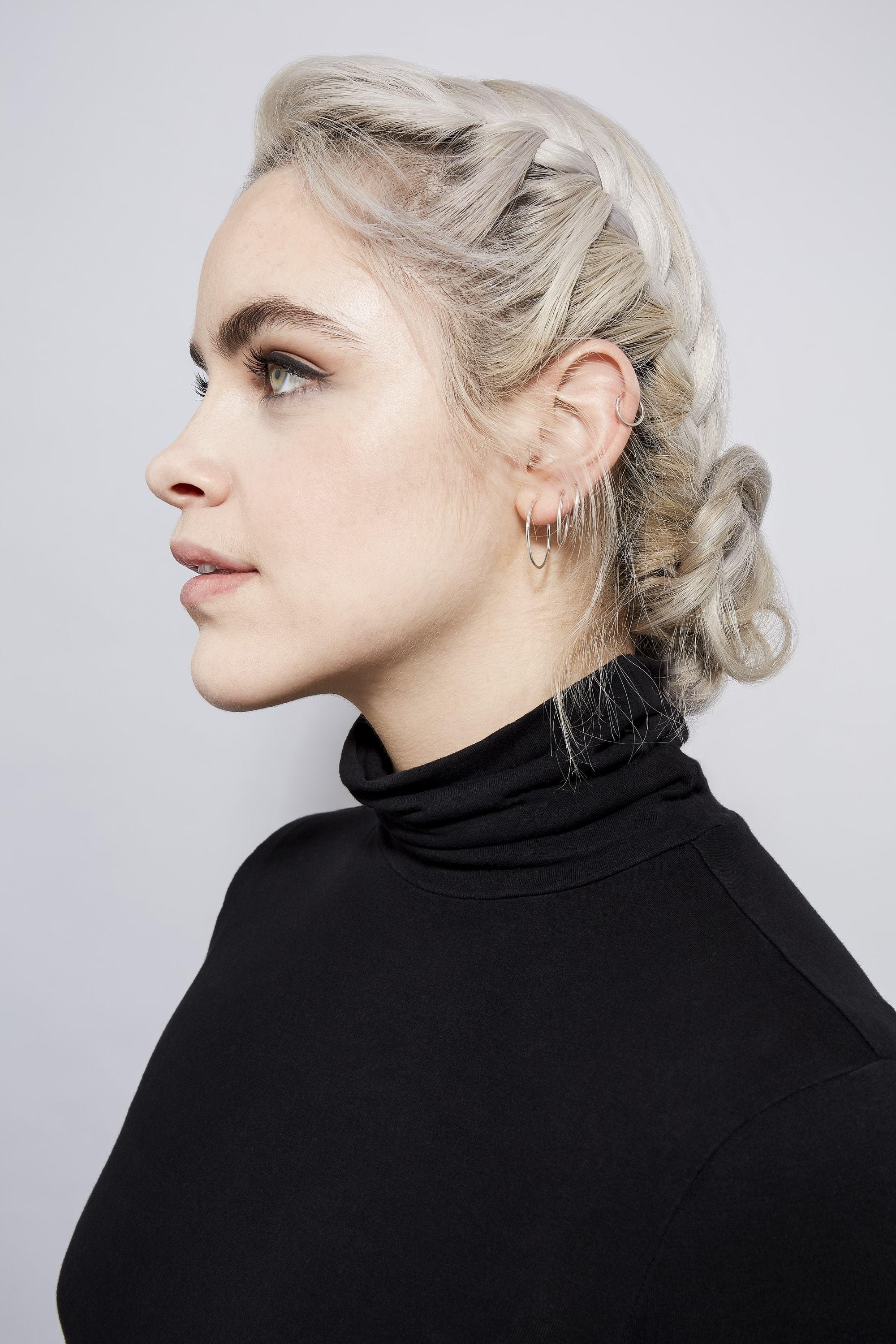 Des tresses faciles pour les cheveux longs : Profil latéral d'une femme aux cheveux blonds cendrés dans un chignon tressé, portant un top noir à col roulé