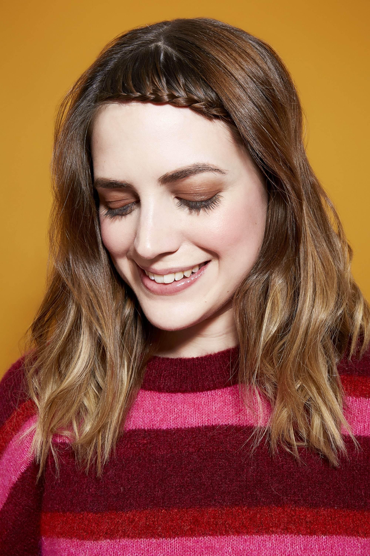 Des tresses faciles pour les cheveux longs : Femme brune à la frange tressée, portant un pull rayé rose et bordeaux