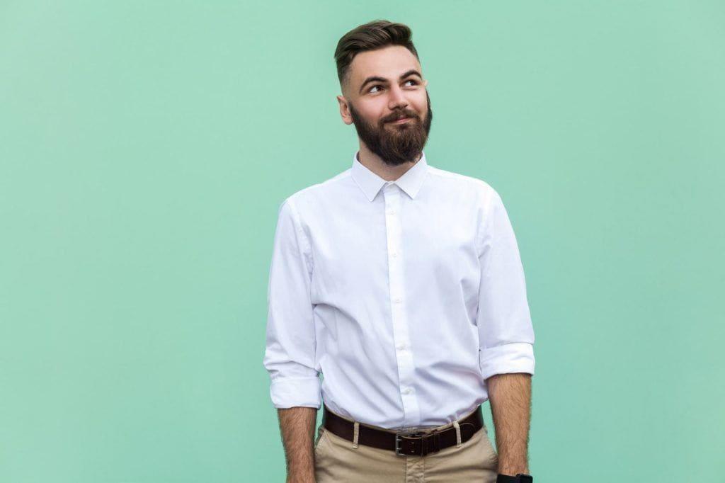 Peigne conique sur une coupe de cheveux : Homme aux cheveux bruns, coiffé d'une coupe effilée en arrière, portant une chemise blanche bordée d'un pantalon beige et se tenant devant un fond vert menthe