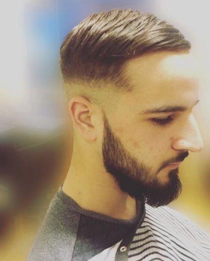 gros plan sur le côté d'un type aux cheveux bruns avec une coupe de cheveux en peigne avec un décollement de peau sur les côtés et une barbe courte
