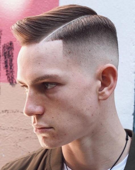 Peigne conique sur une coupe de cheveux : Un homme aux cheveux bruns avec un peigne effilé sur une coupe de cheveux avec des détails de décoloration
