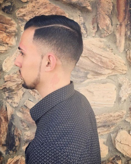 profil latéral d'un type brun portant une chemise élégante avec un peigne effilé sur une coupe de cheveux