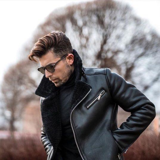homme brun se tenant dehors devant un arbre, portant une veste en cuir et des mèches de cheveux avec un peigne effilé qui a poussé sur une coupe de cheveux