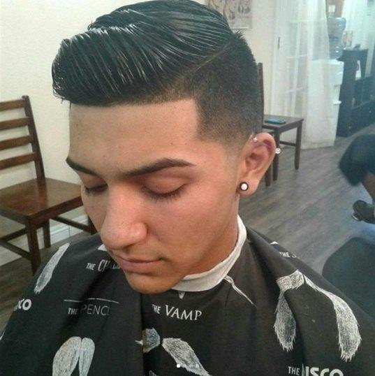 photo du haut d'un homme brun dans le fauteuil du coiffeur avec un peigne effilé sur une coupe de cheveux coiffée au gel wet look