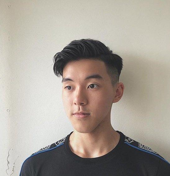 Peigne conique sur une coupe de cheveux : Homme aux cheveux foncés, coiffure au peigne fin avec un dégradé de côté rasé