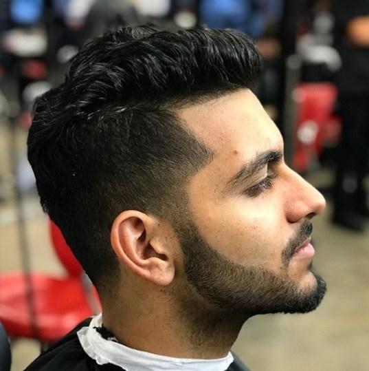 gros plan latéral d'un homme aux cheveux bruns avec une longue coupe au peigne fin et des poils faciaux soignés