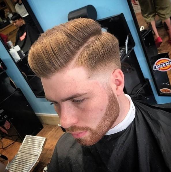 Peigne conique sur une coupe de cheveux : Photo de coiffeur d'un homme roux avec un peigne sur une coupe de cheveux effilée avec des poils sur le visage