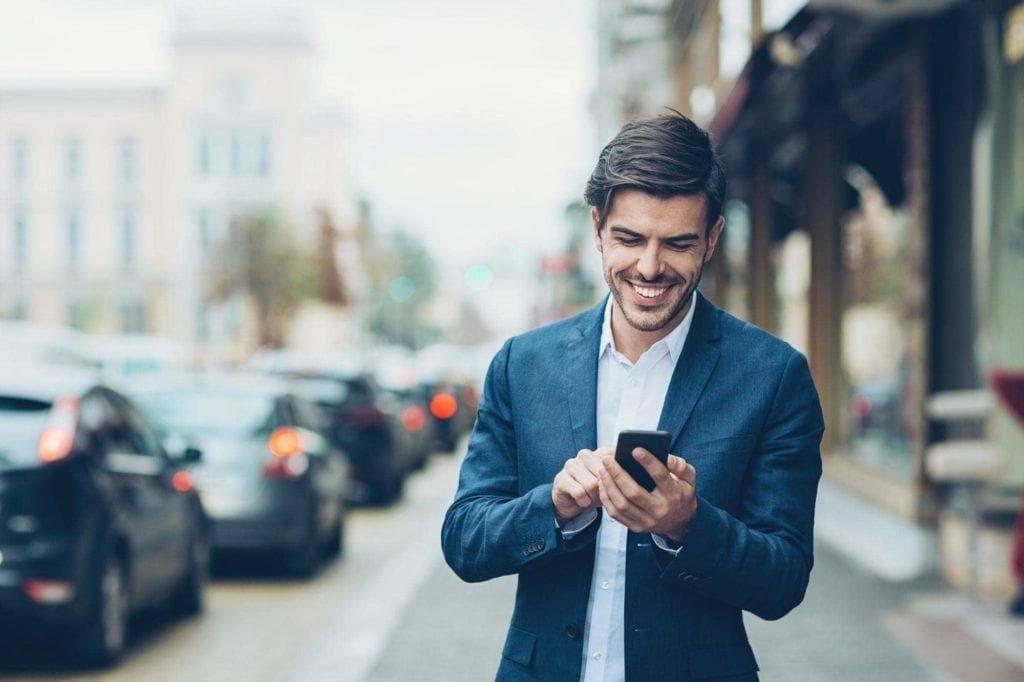 Peigne conique sur une coupe de cheveux : Photo d'un homme dans la rue, cheveux bruns, coiffé d'un peigne effilé subtil, portant un costume bleu marine et utilisant son téléphone