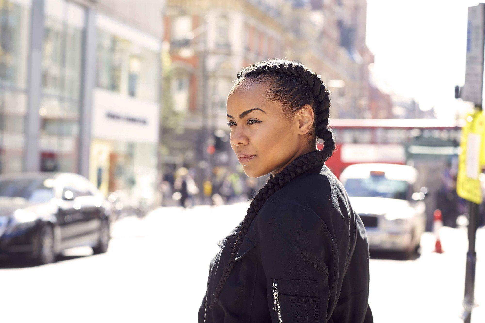 Coiffures d'hiver pour cheveux naturels : Vue latérale d'une femme avec des tresses de boxer double marron foncé, portant une veste de bombardier noire et se tenant dans la rue