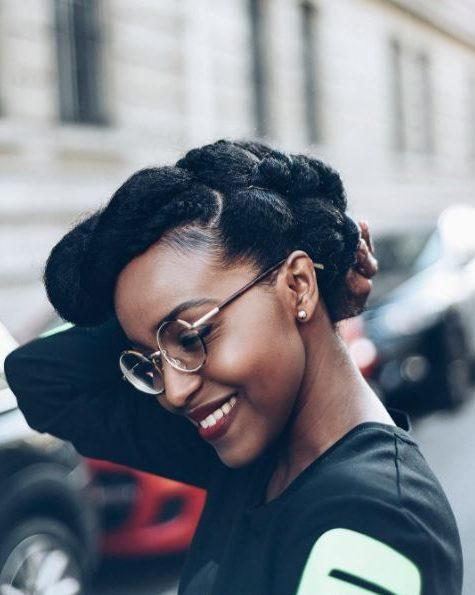 Coiffures d'hiver pour cheveux naturels : Femme souriante aux cheveux naturels foncés dans un style pompadour tordu, portant des lunettes et posant dans la rue