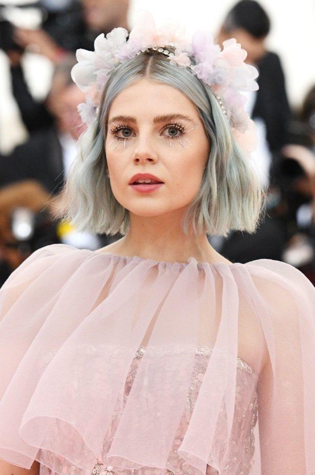 Lucy Boynton avec un bob bleu ondulé avec un bandeau floral