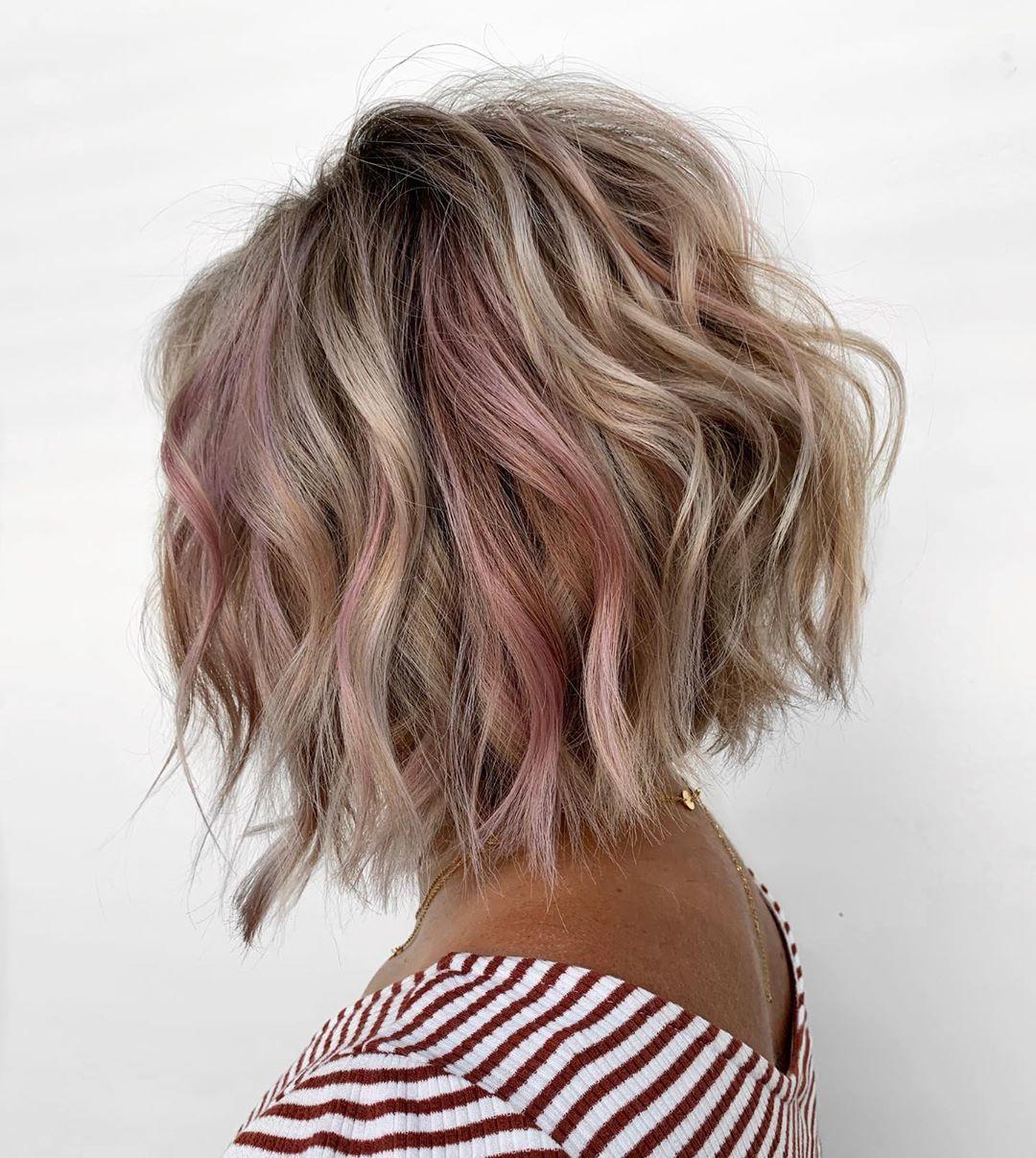 Femme blonde avec un bob ondulé et empilé à reflets roses