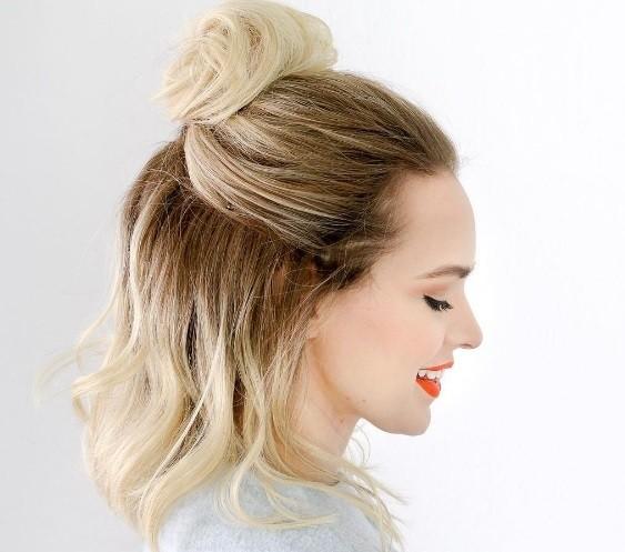 Coiffures courtes blondes : modèle avec des cheveux courts en lobes d'ombre blonds coiffés en chignon mi-hauteur