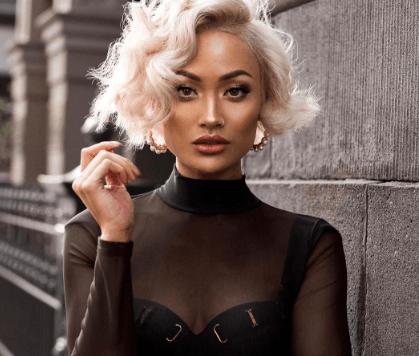 modèle avec une courte coiffure blonde bouclée dans la rue avec une tenue noire