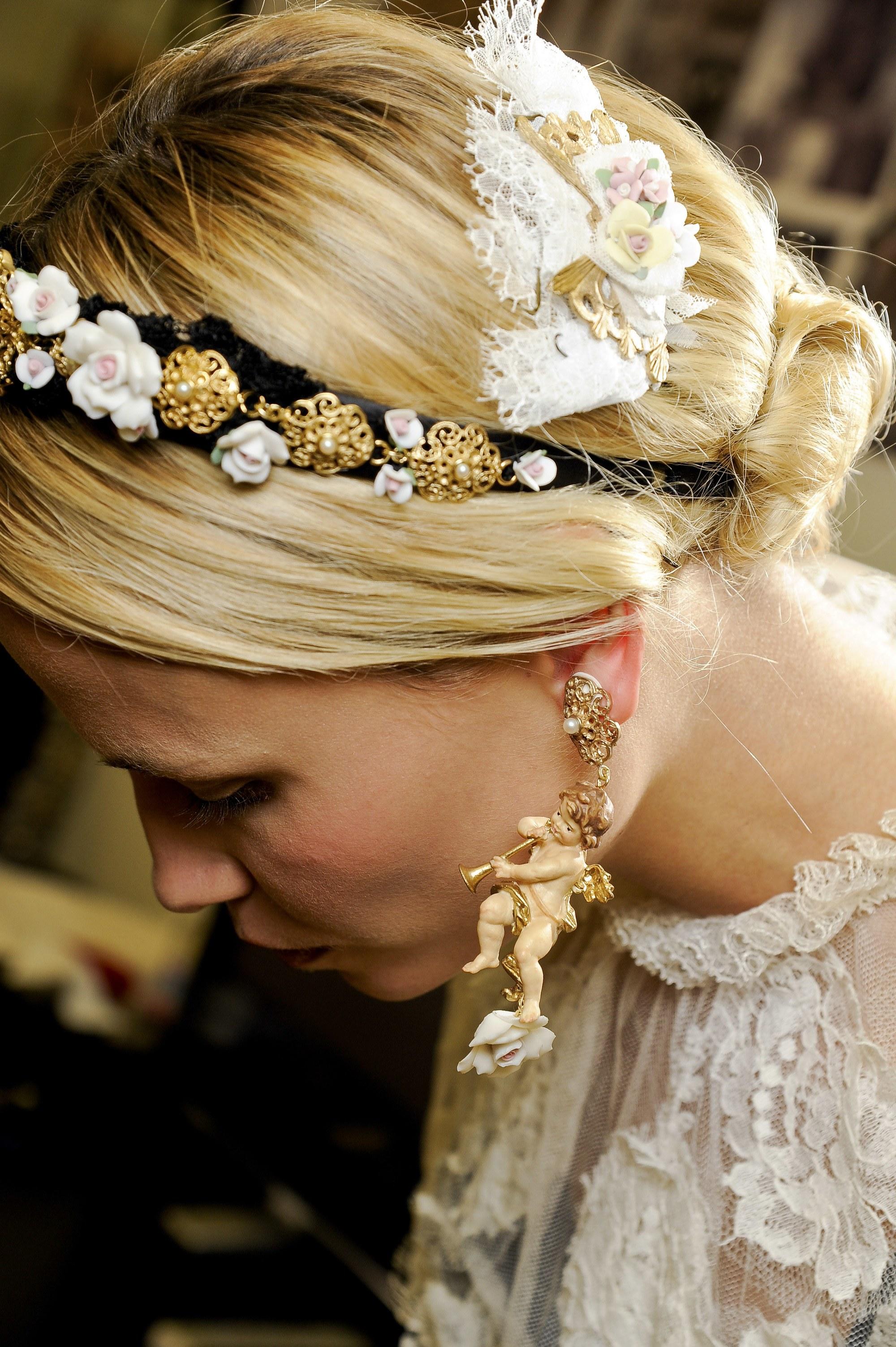 modèle avec une courte coiffure blonde au salon dolce gabbana avec un chignon bas et des accessoires