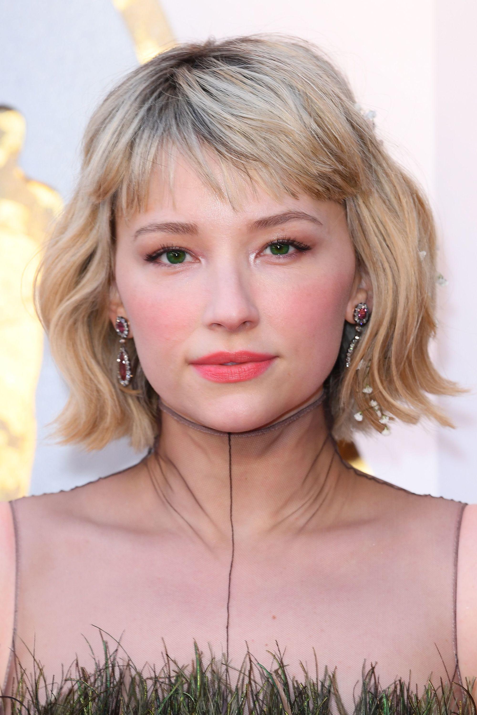 Coupes de cheveux courtes avec frange : Haley Bennett avec un bob ondulé blond avec une frange latérale courte sur un tapis rouge.