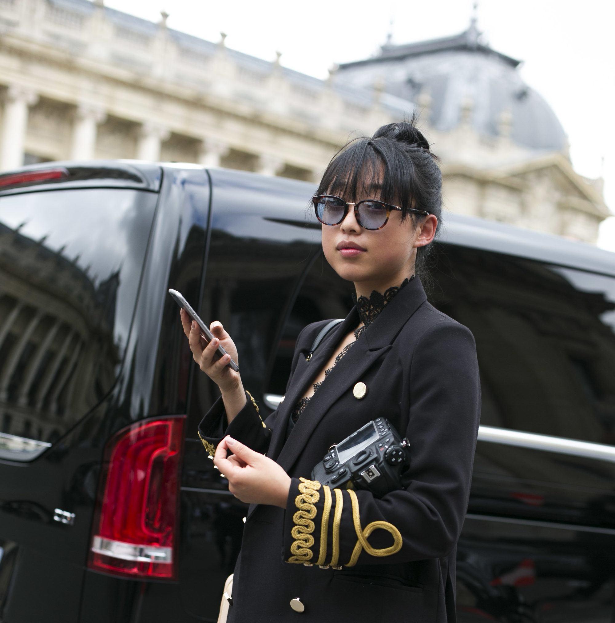 photo de rue d'une femme aux cheveux courts et à la longue frange portant une tenue noire et des lunettes