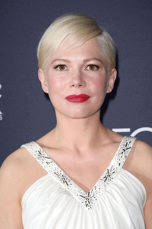 Coupes de cheveux courtes avec frange : Michelle Williams avec une robe blanche et un rouge à lèvres rouge, en blonde platine, coupe courte et droite, avec une frange sur le côté