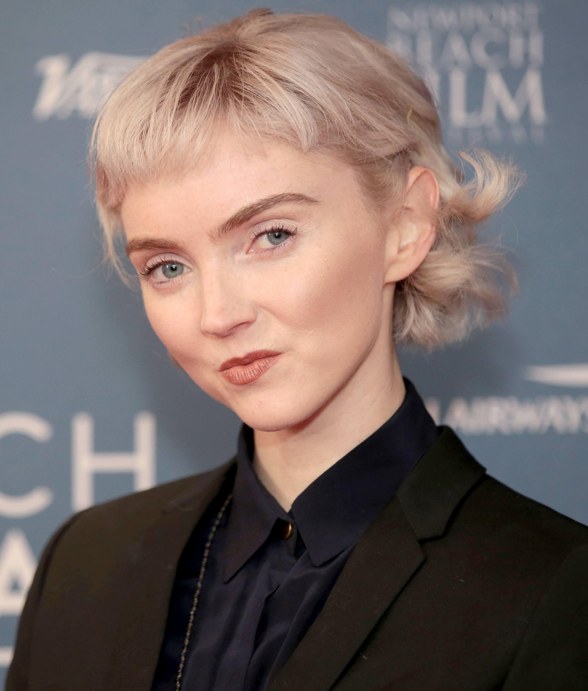 Coupes de cheveux courtes avec frange : Lily Cole, blonde décolorée, cheveux courts et ondulés avec microfranges, portant une chemise noire et un blazer.