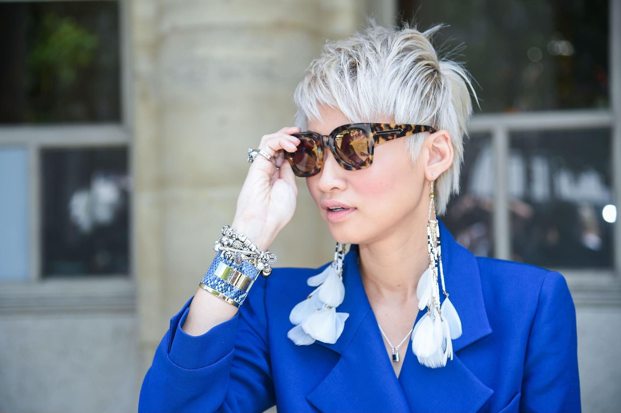 modèle de rue aux cheveux courts et à la coiffure à longue frange, portant des lunettes de soleil et une veste bleue
